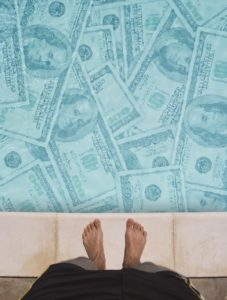 Man standing at the edge of a pool full of money.